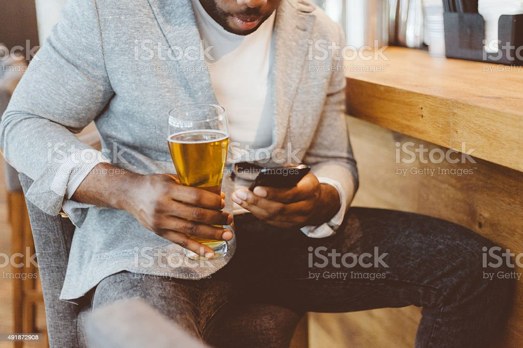 Afro american man sitting in the pub, using smart phone stock photo