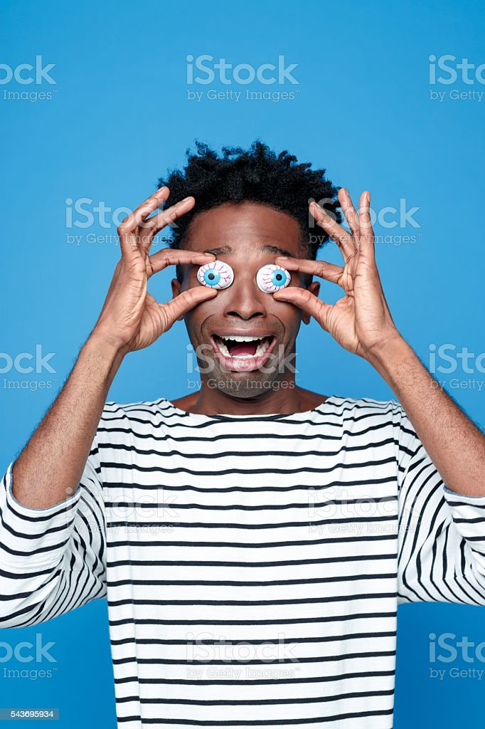 Afro american young man wearing funny eyes mask stock photo