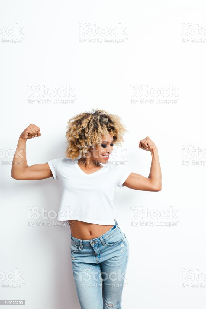 Afro american young woman flexing arms stock photo