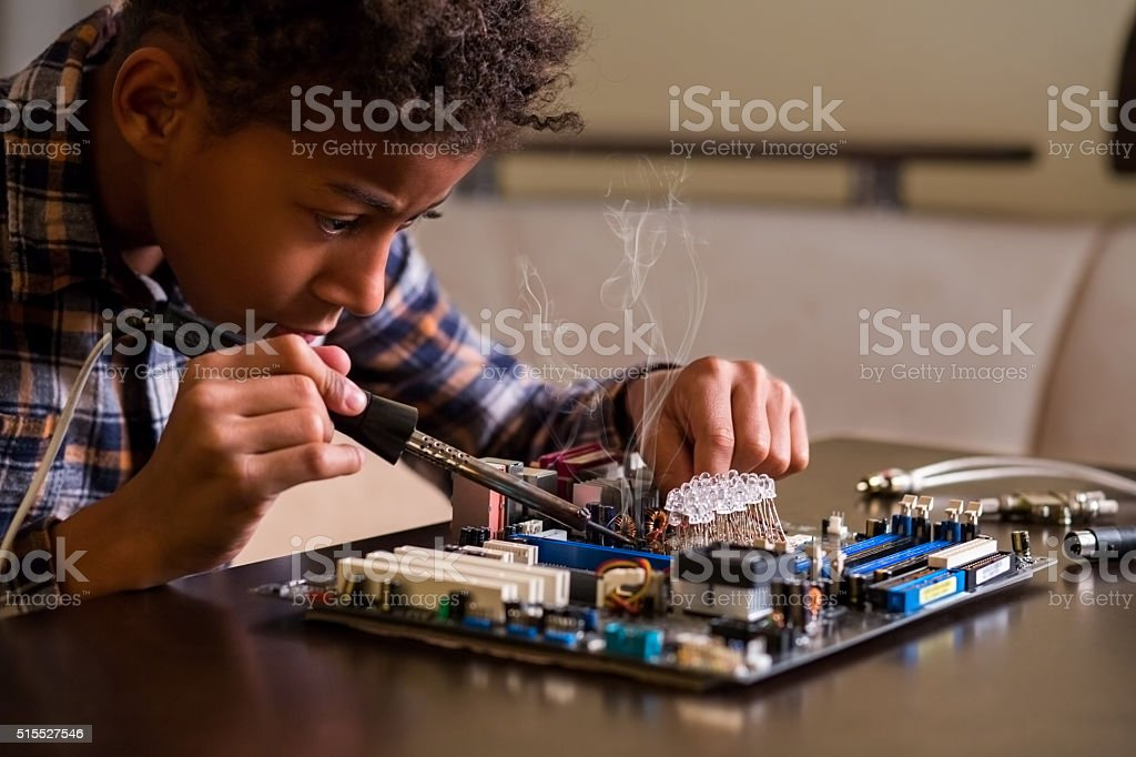 Afro boy fixing motherboard. stock photo