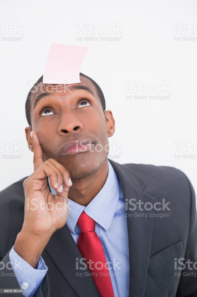 Afro businessman with blank note on forehead stock photo