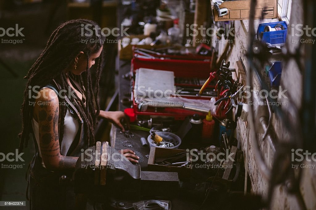 Afro craftswoman assembling bicycle parts at her work bench stock photo