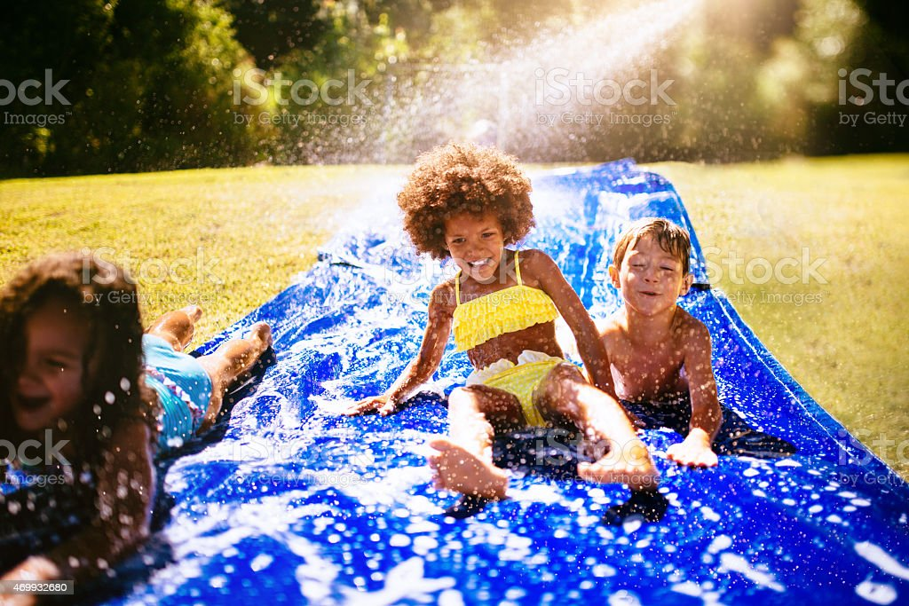 Afro girl and friends playing on a water slide stock photo