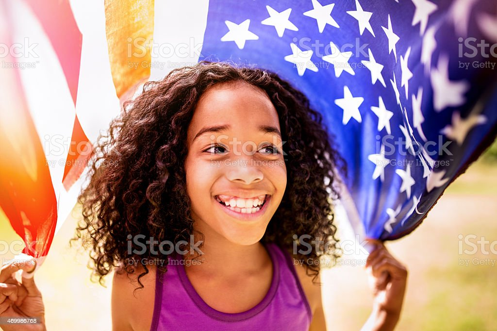 Afro girl happily holding an American flag stock photo