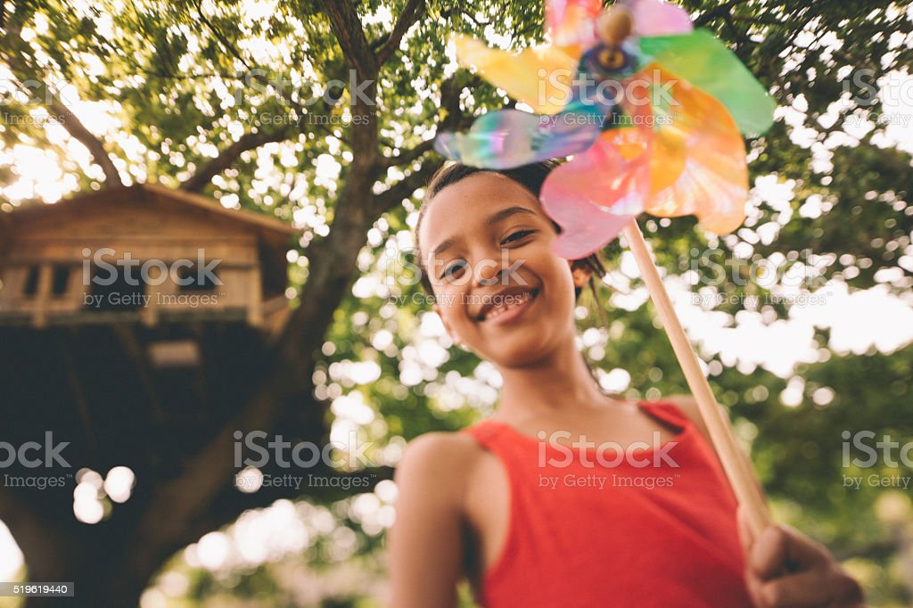 Afro girl playing with a windmill under treehouse in tree stock photo