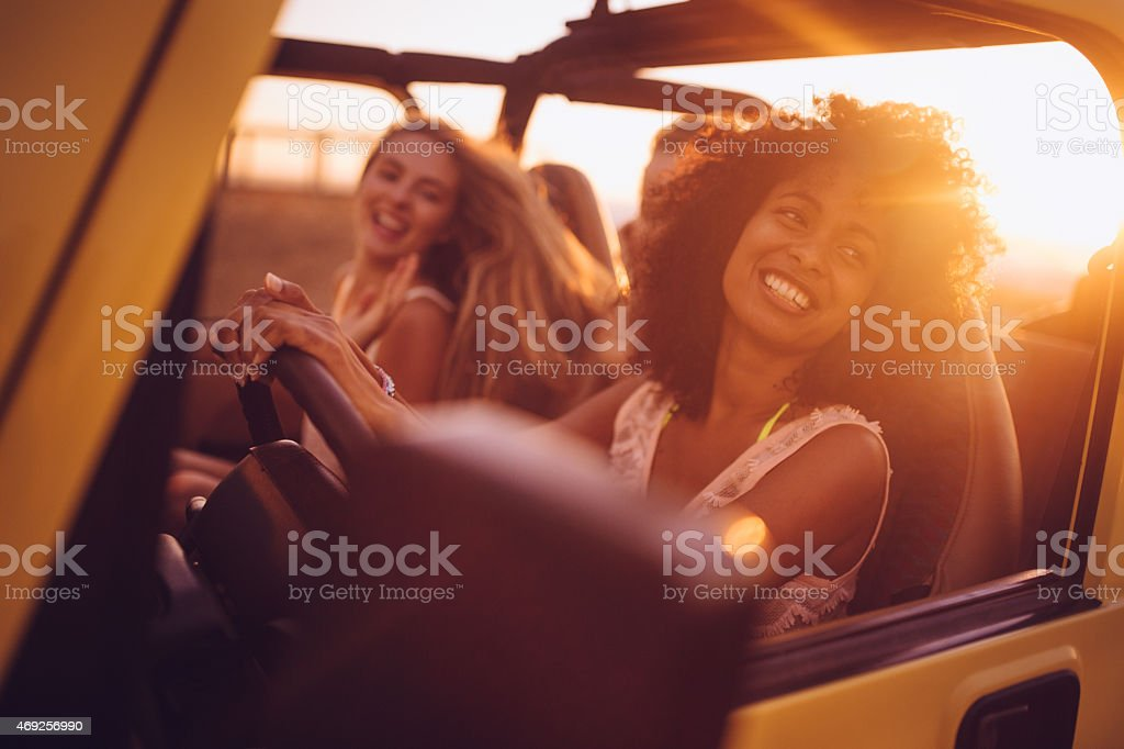Afro girl with friends on a road trip at sunset stock photo