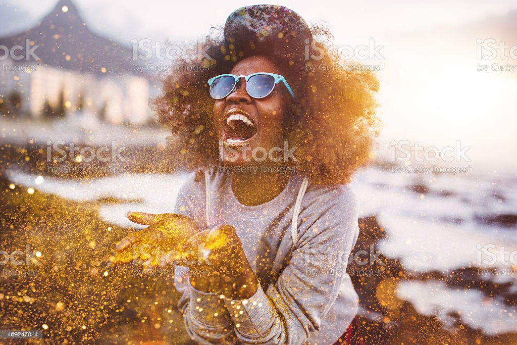 Afro hipster girl laughing ecstatically while throwing gold glitter stock photo
