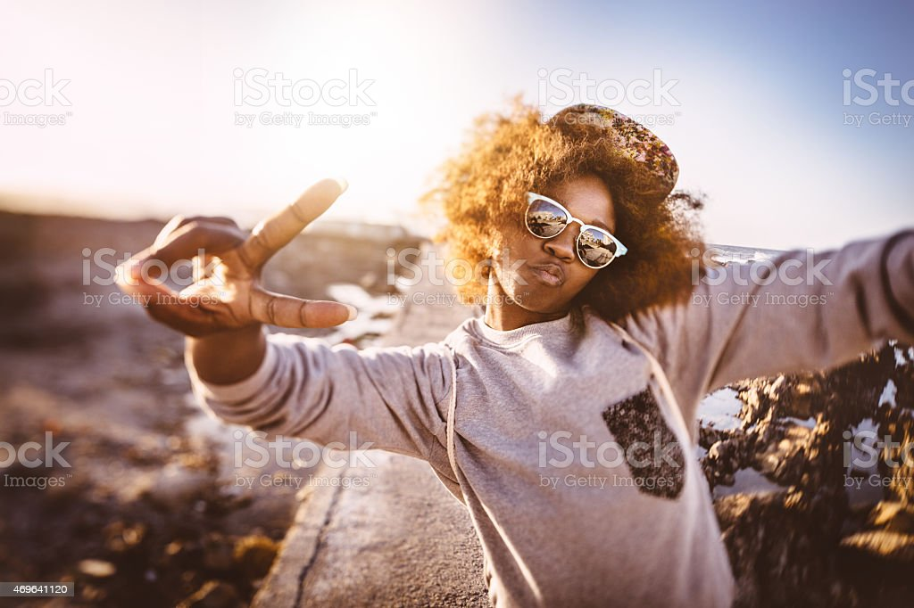Afro hipster teen showing peace sign while at the beach stock photo