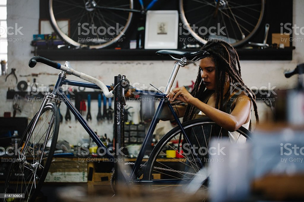 Afro woman bicycle mechanic recpairing a bike in her workshop stock photo