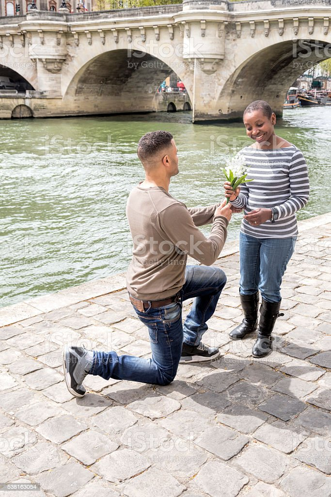 Afro-american man proposing to woman of African decent by Seine stock photo