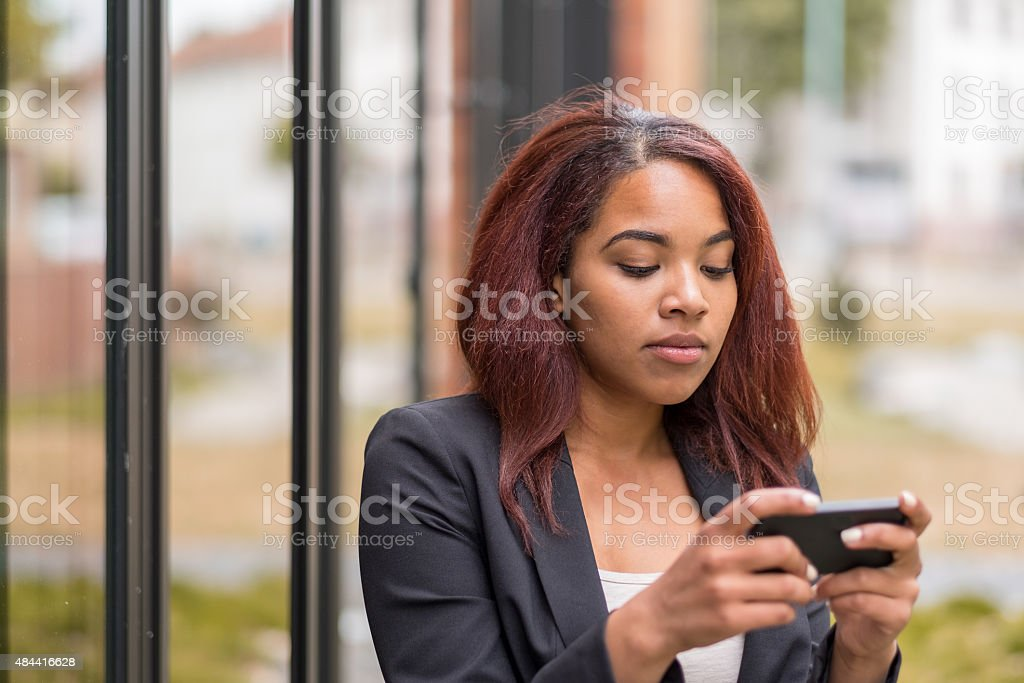 Afro-American Office Woman Texting on her Phone stock photo