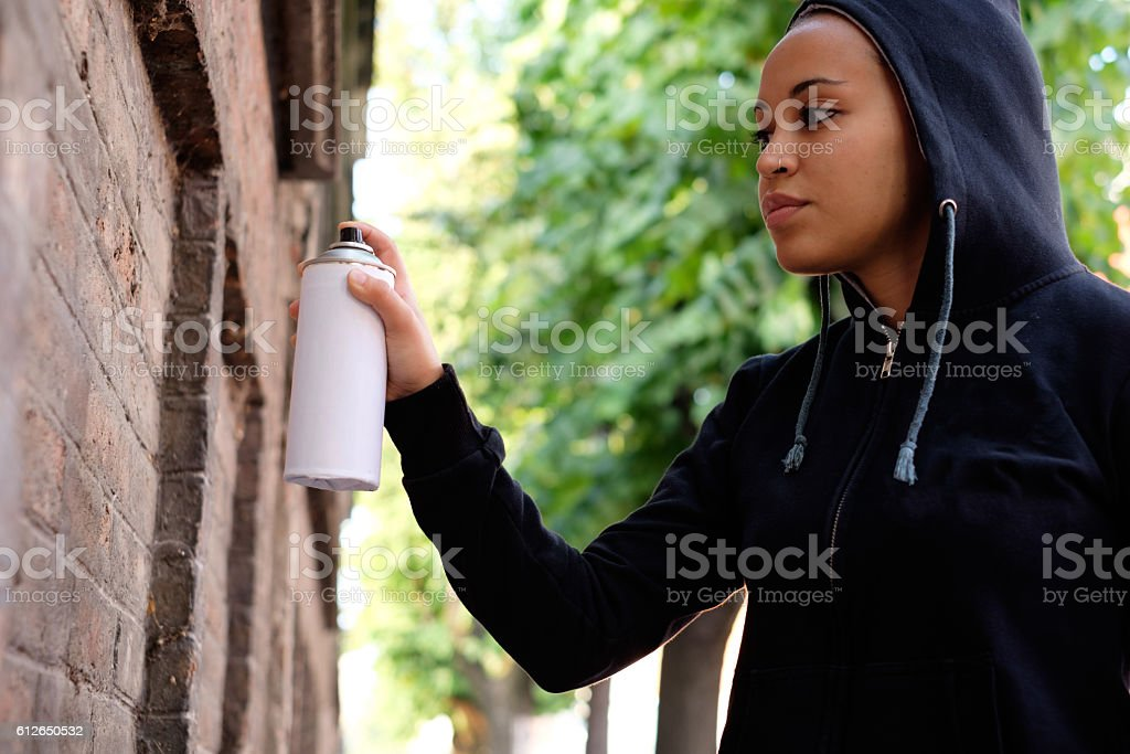 Afro-american woman using spray paint stock photo
