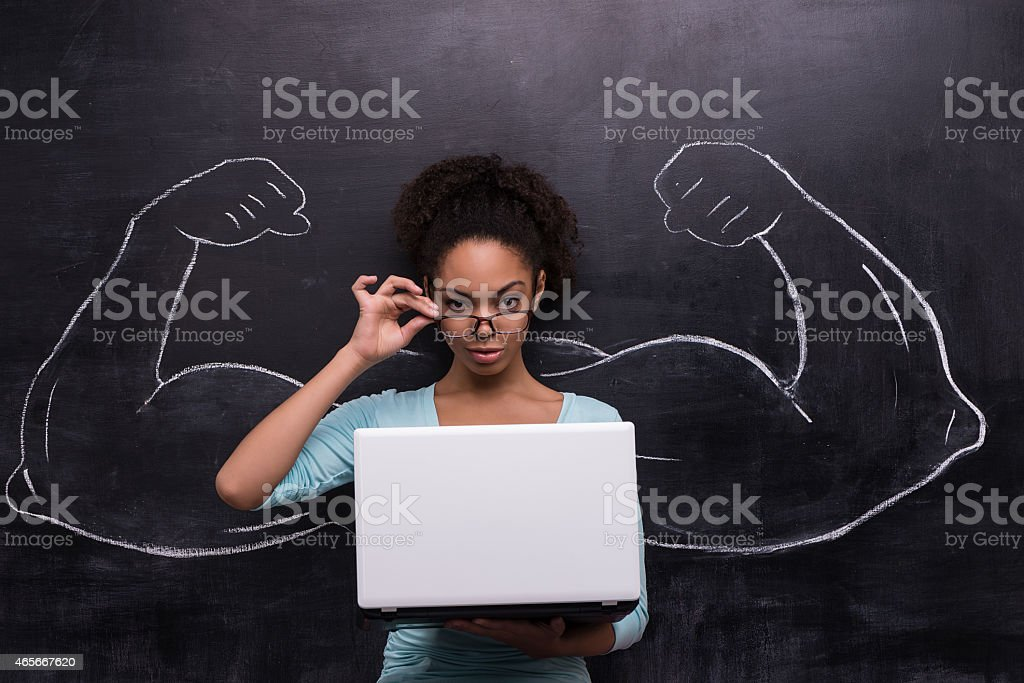 Afro-american woman with laptop and painted muscular arms on chalkboard stock photo