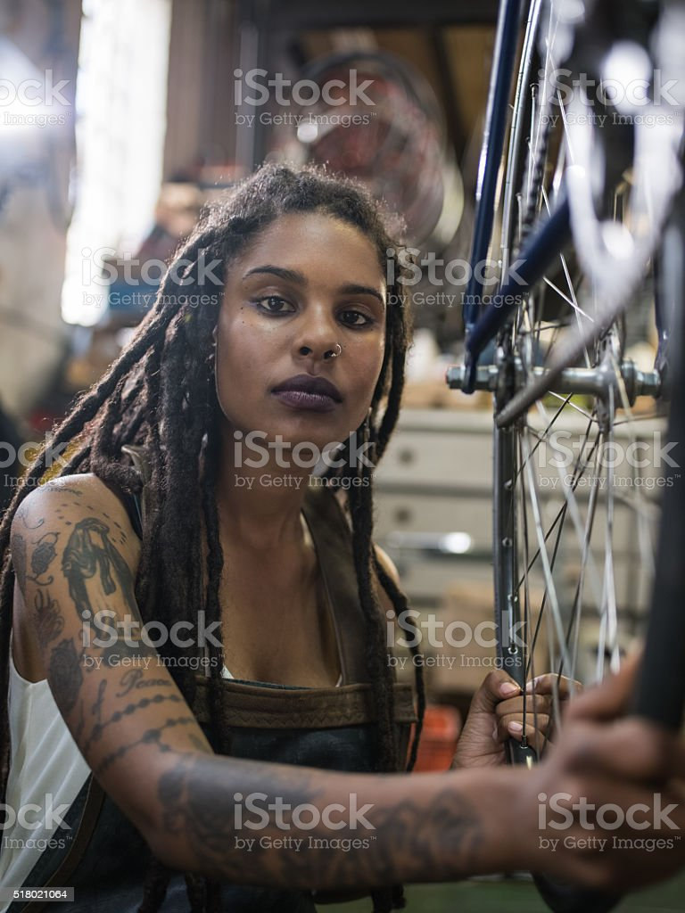 Afro-american woman with tattoos and dreadlocks in a repairs wor stock photo