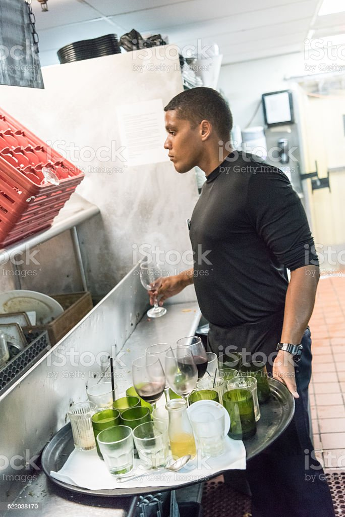 Afro-caribbean waiter busboy working at the kitchen stock photo