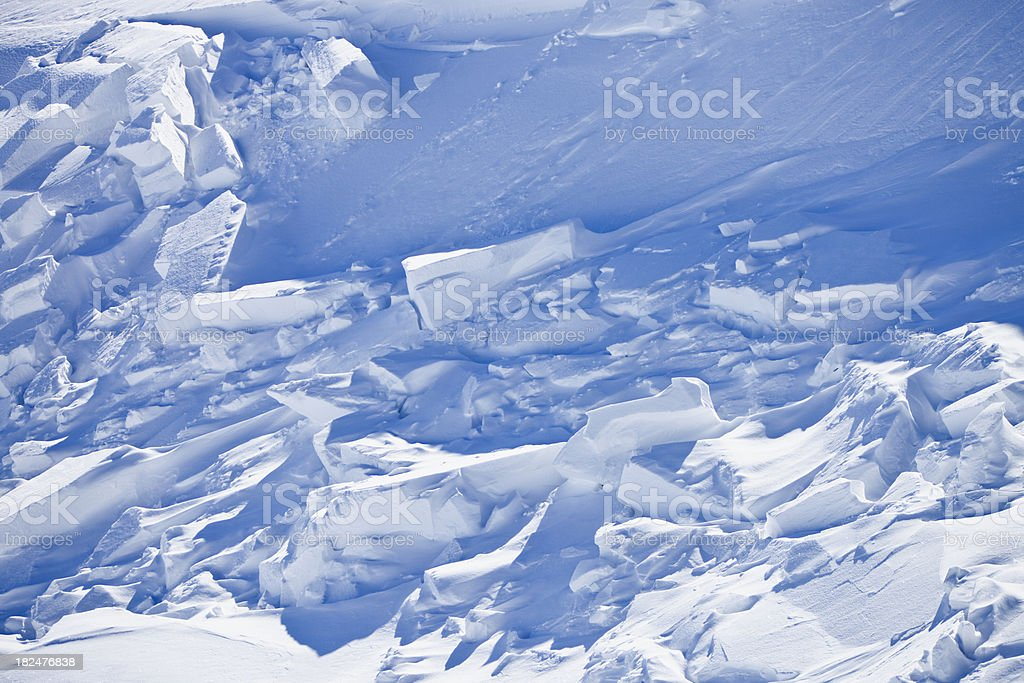 After avalanche, crushed snow parts on slope in winter stock photo