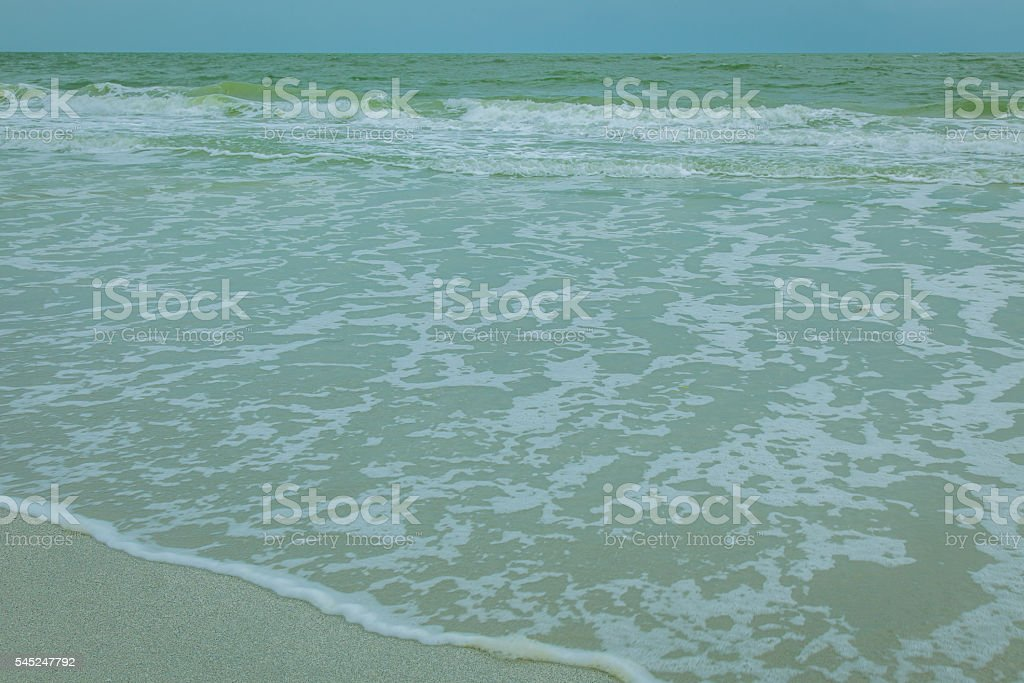 Afternoon ocean view with small waves near beach stock photo