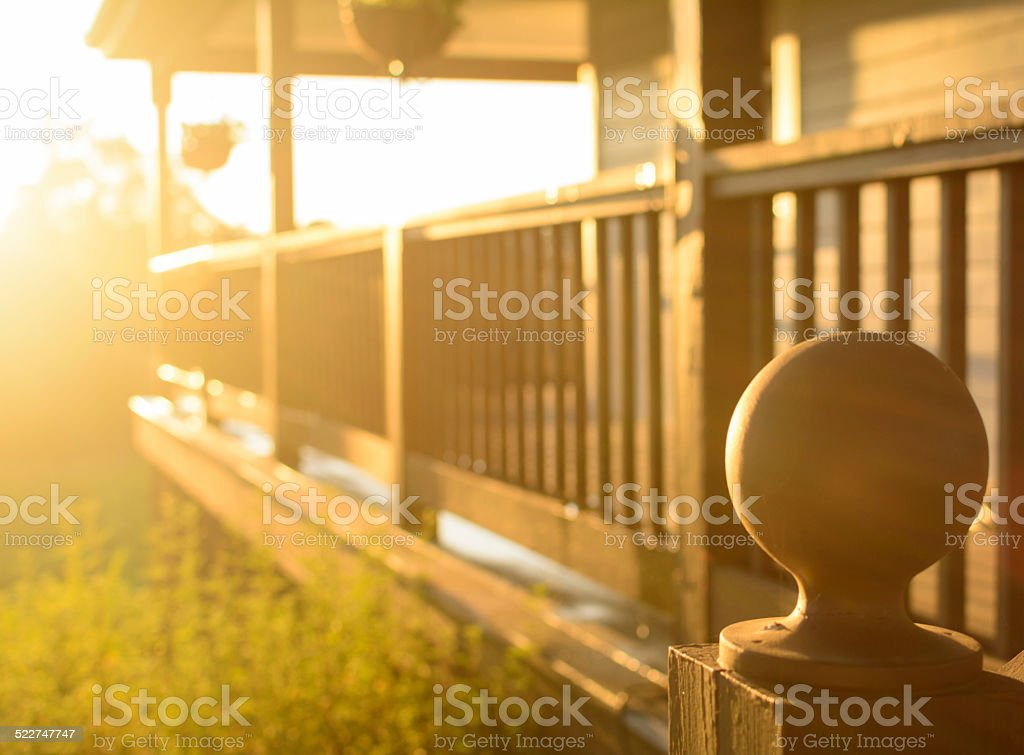 Afternoon rays of sun against a wooden porch stock photo