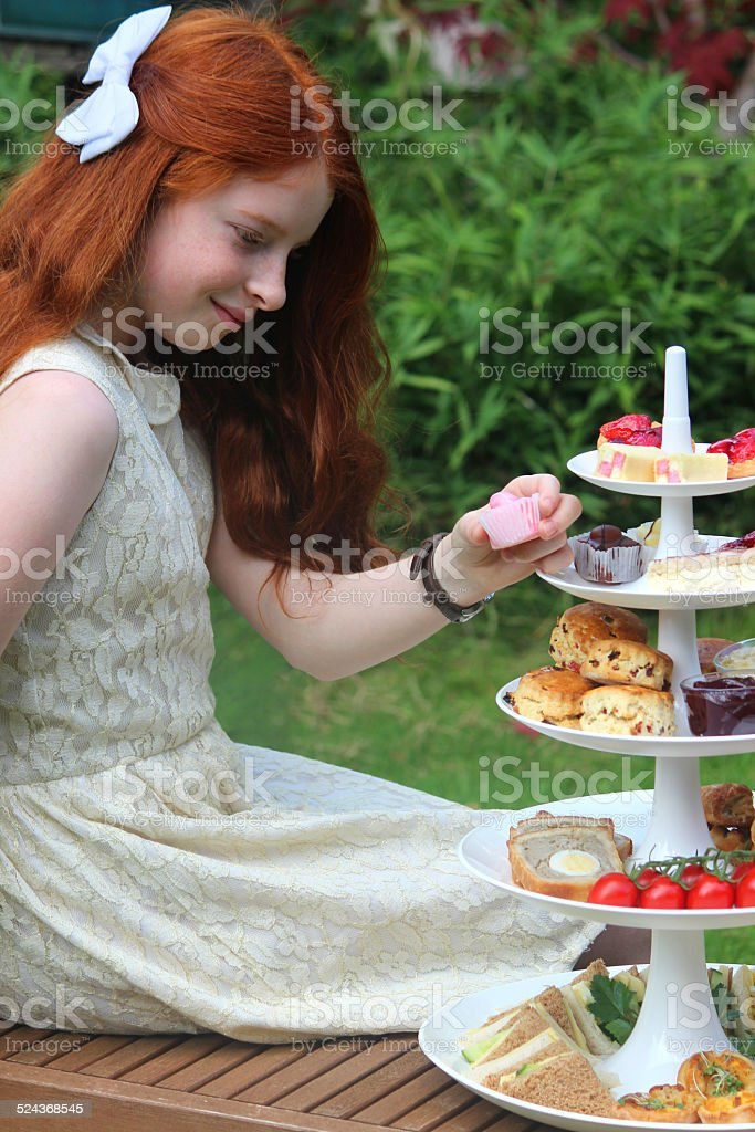 Afternoon tea / cream tea, cake stand tiers, girl eating cakes-scones-sandwiches stock photo