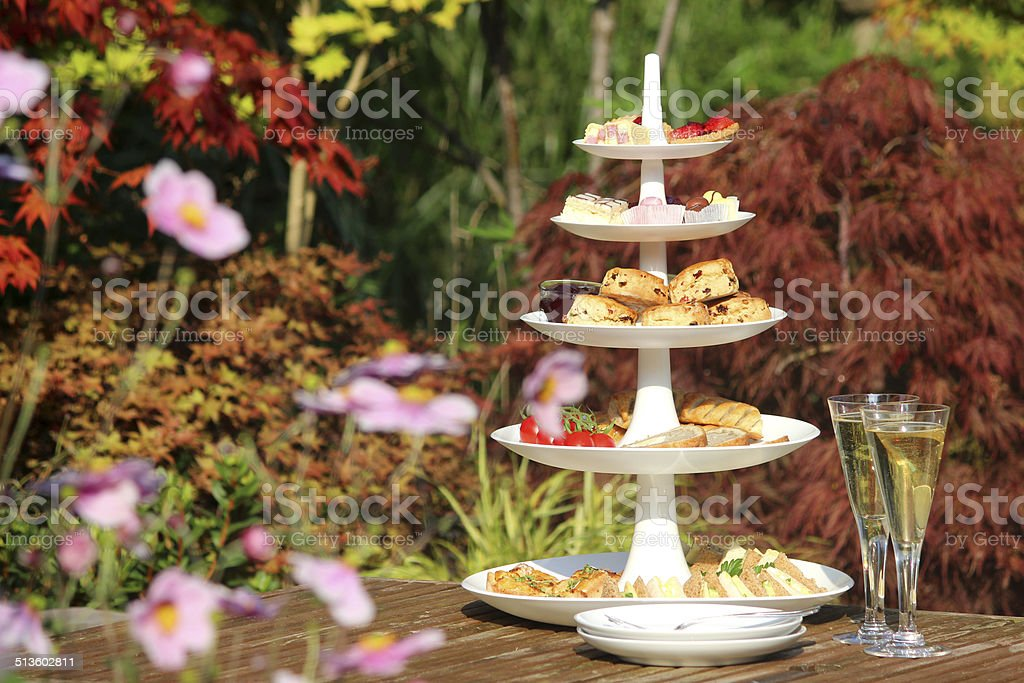 Afternoon tea / cream tea, tiered cake-stand, sandwiches, cakes, scones, garden stock photo
