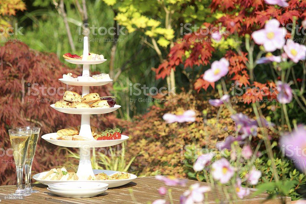 Afternoon tea / cream tea, tiered cake-stand, sandwiches, cakes, scones, garden stock photo