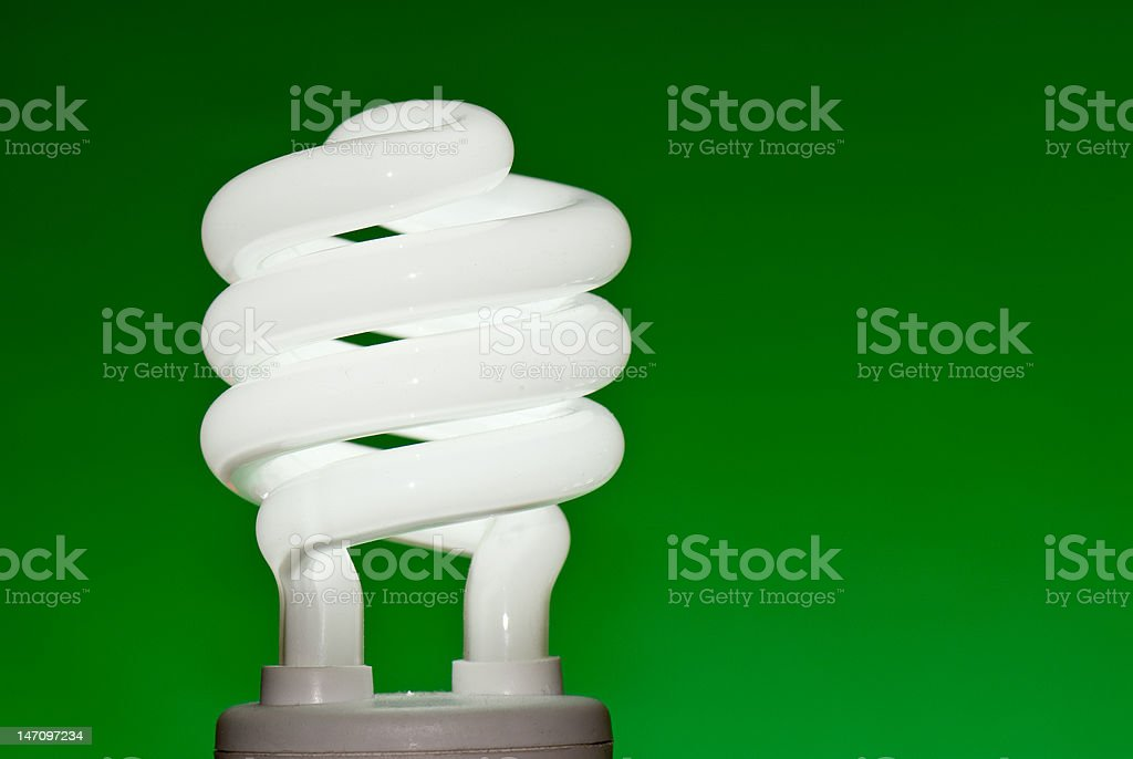 CFL (Compact fluorescent lightbulb) against a green background royalty-free stock photo