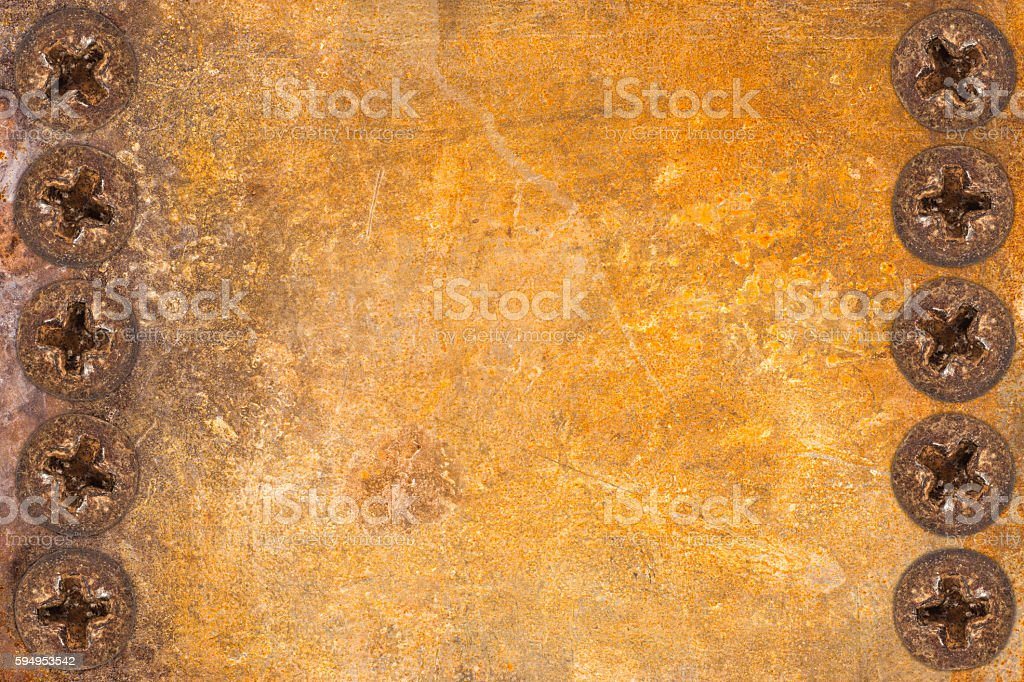 aged and weathered rusty metallic panel with screws stock photo