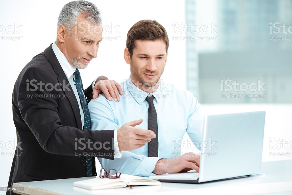 Aged and young businessmen having meeting stock photo