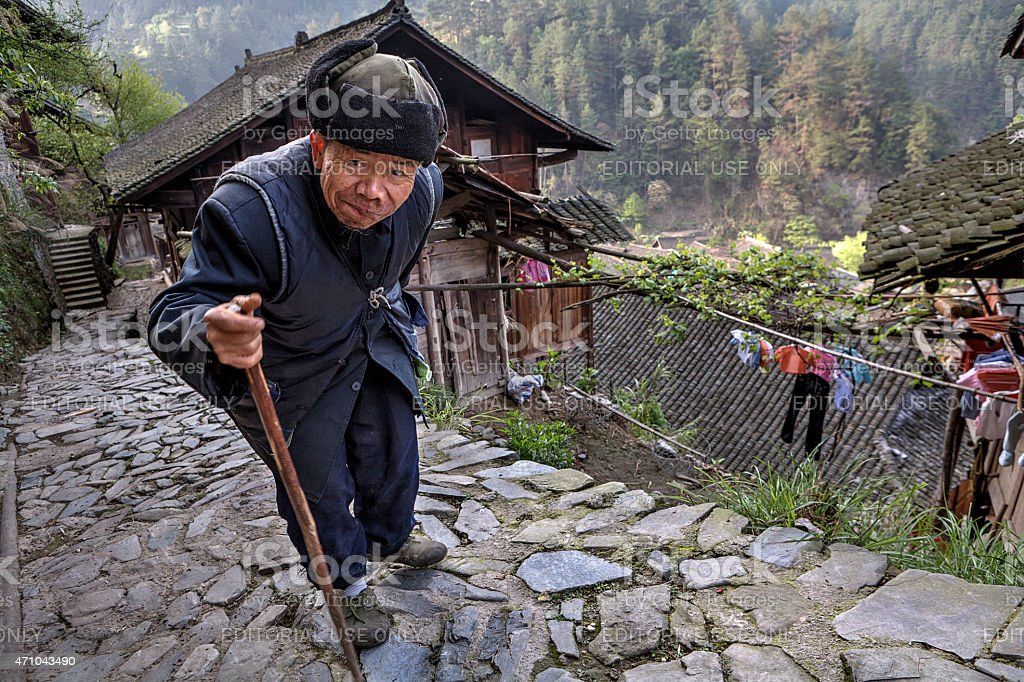 Aged Asian walks along stone road, laying on his stick. stock photo