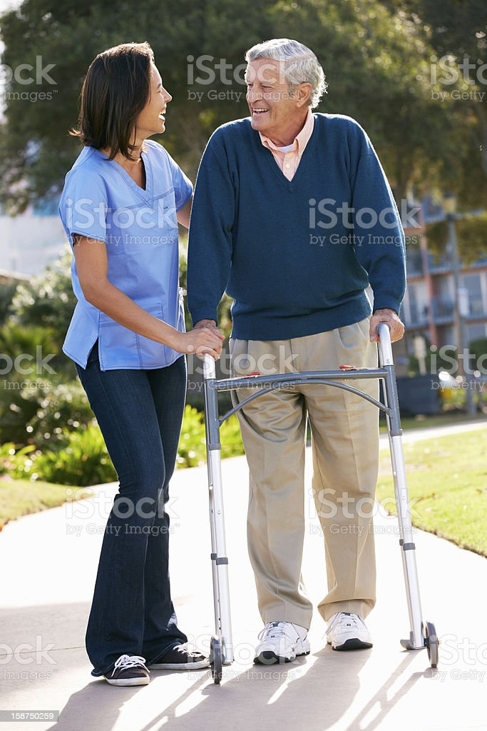 Aged care  helping senior man with walking frame stock photo