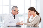 Aged doctor with patient in hospital office