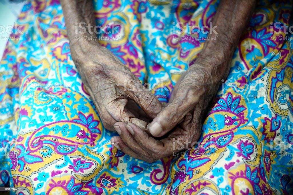 Aged hands on a bright and colorful patterned background stock photo