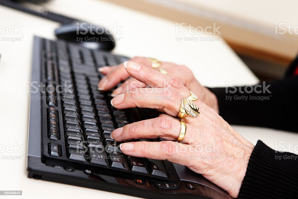 Aged hands on the computer keyboard (XXL) stock photo
