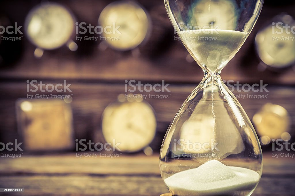 Aged hourglass with flowing sand stock photo
