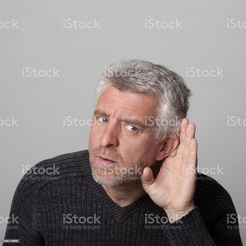 aged man listens with his hand to his ear stock photo