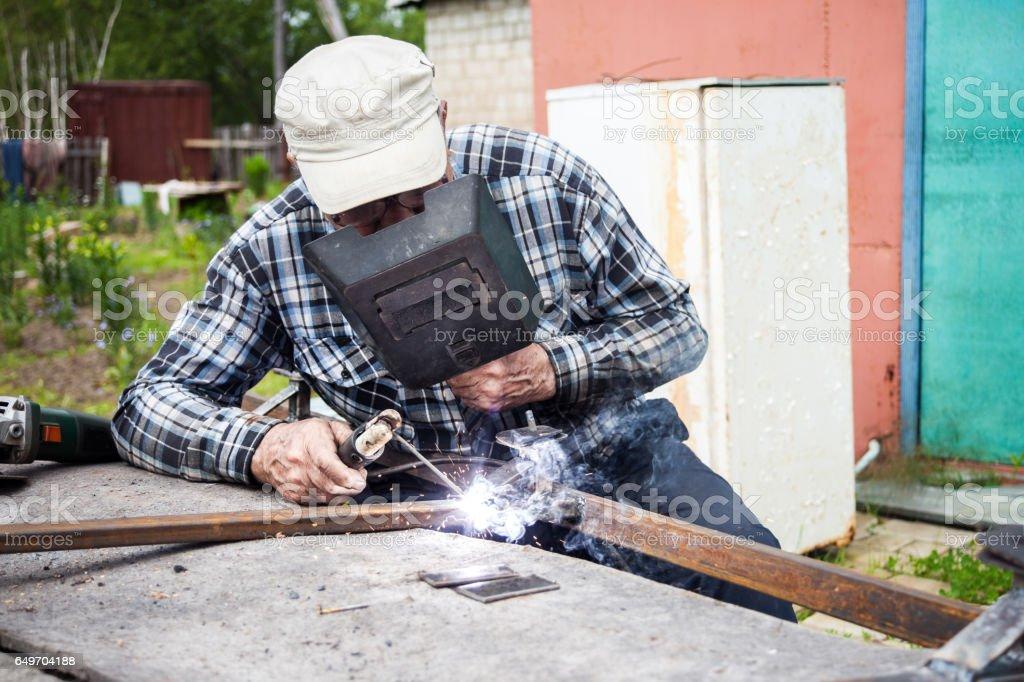 Aged man welding metal construction stock photo