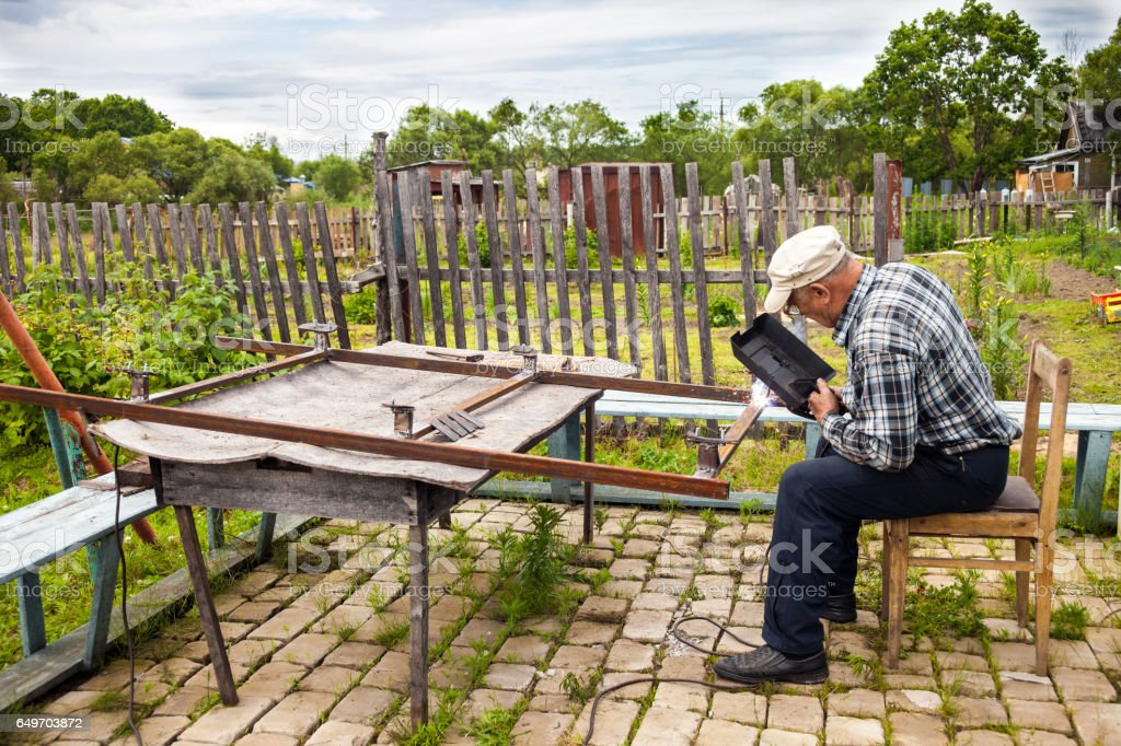 Aged man welding metal structure stock photo