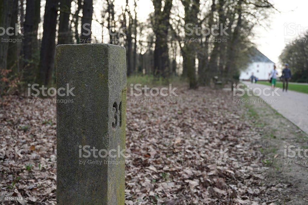 Aged stony milestone next to the touristy pathway stock photo