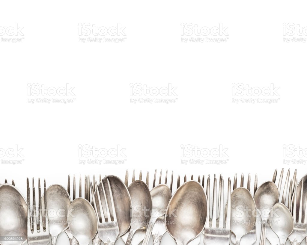 Aged vintage silver forks and spoons border isolated stock photo