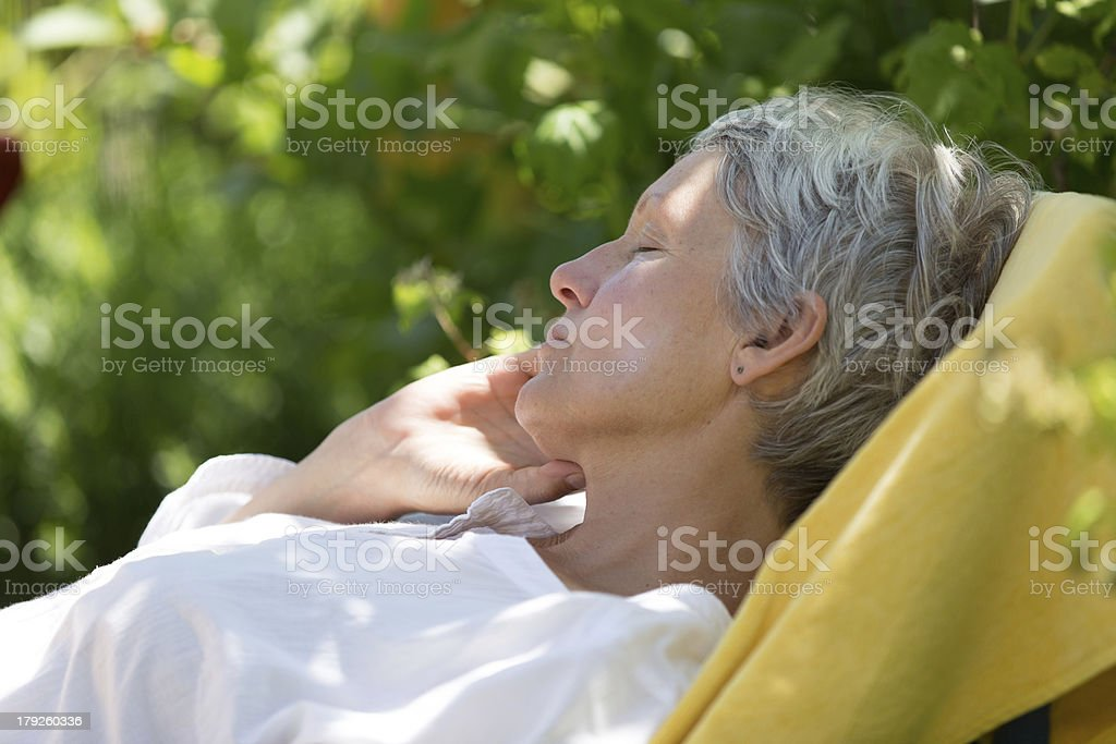 Aged woman sleeping on lounger royalty-free stock photo