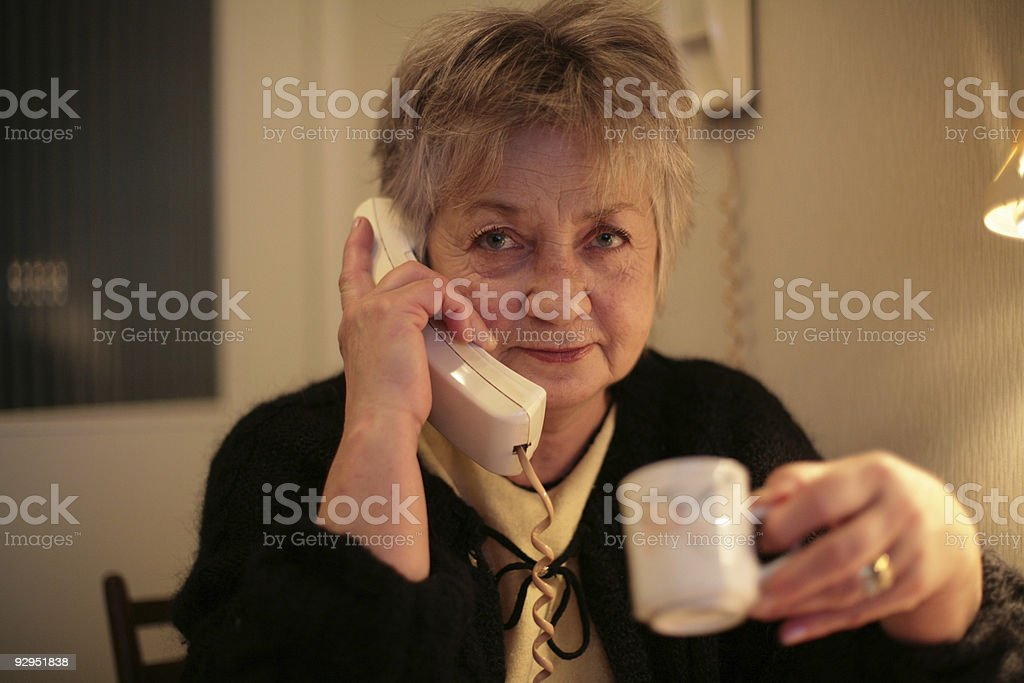 aged woman speaking phone and drinking coffee royalty-free stock photo