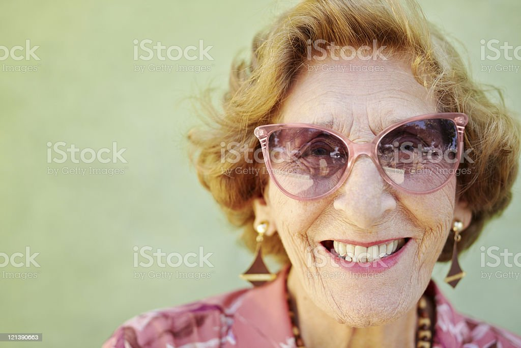 aged woman with pink eyeglasses smiling at camera stock photo