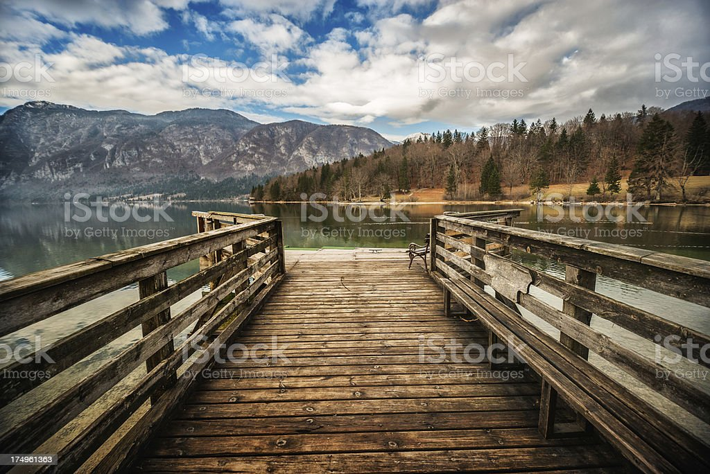 Aged Wooden Pier Deck on Lake Deep in Mountains royalty-free stock photo