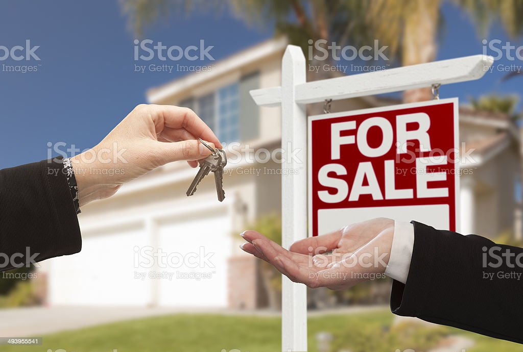Agent Handing Over House Keys in Front of New Home stock photo