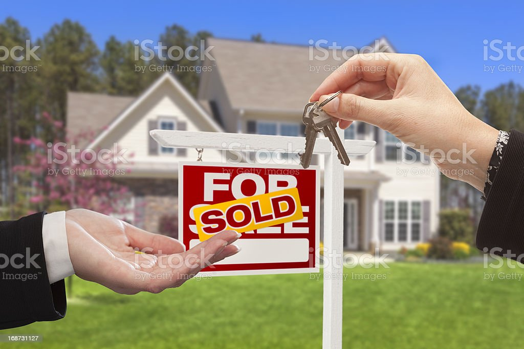 Agent Handing Over the House Keys in Front of Home stock photo