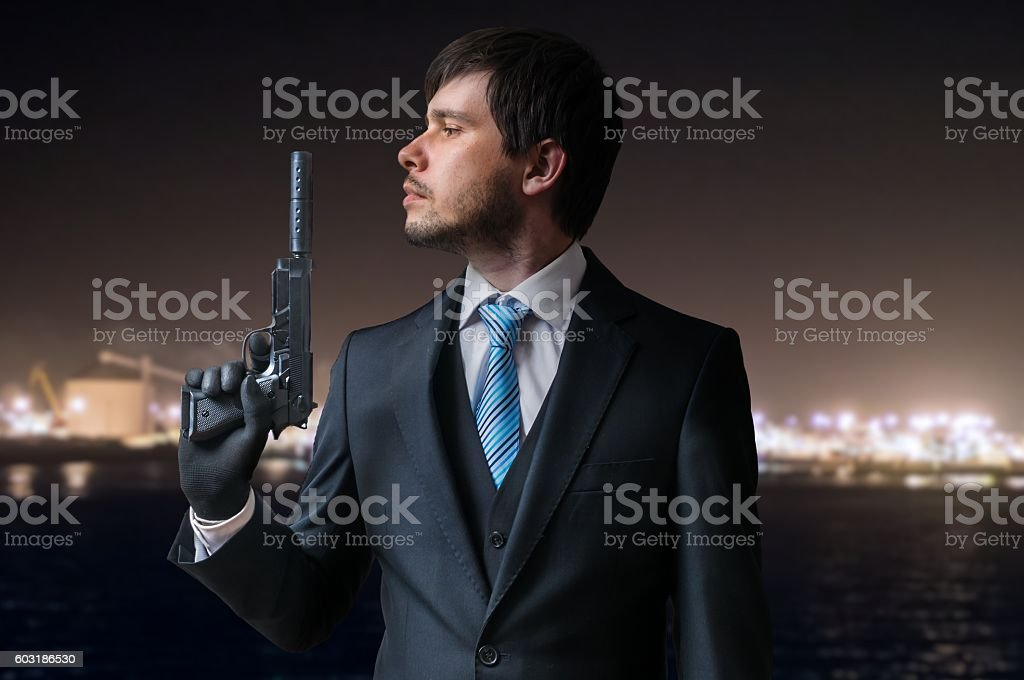 Agent or hitman holds pistol with silencer at night. stock photo