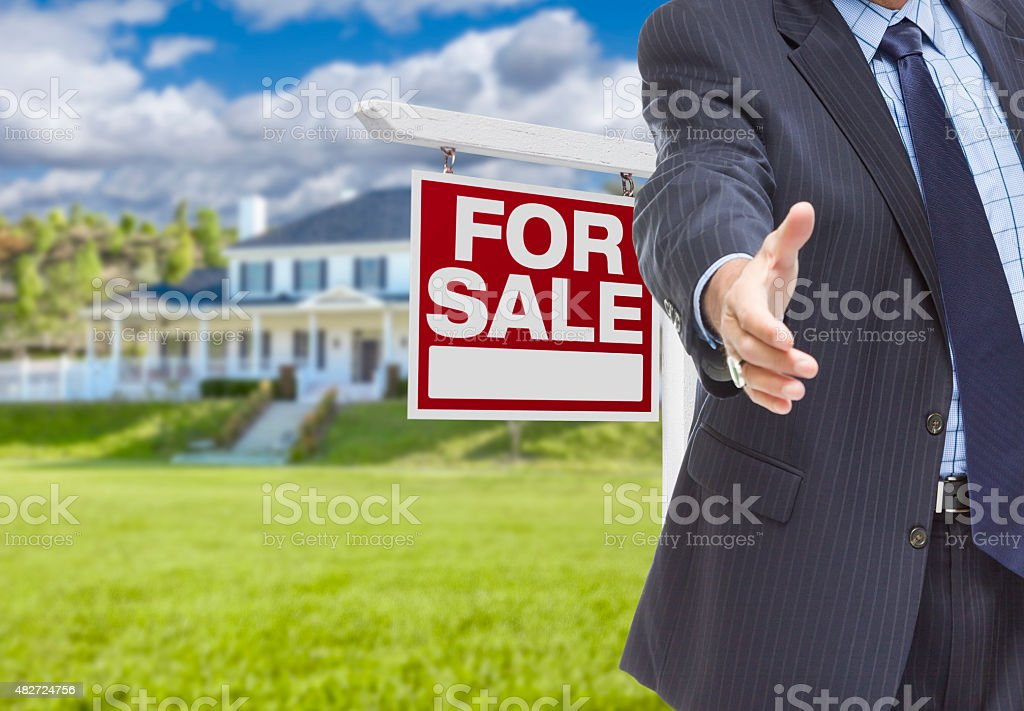 Agent Reaches for Handshake, Sale Sign and House Behind stock photo