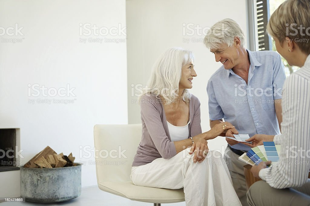 Agent showing color swatches to couple royalty-free stock photo