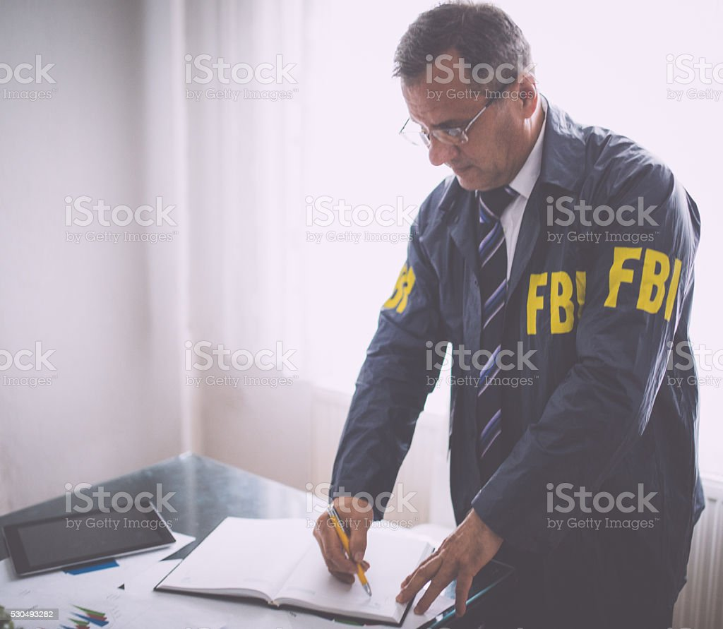FBI agent signing papers at his office stock photo