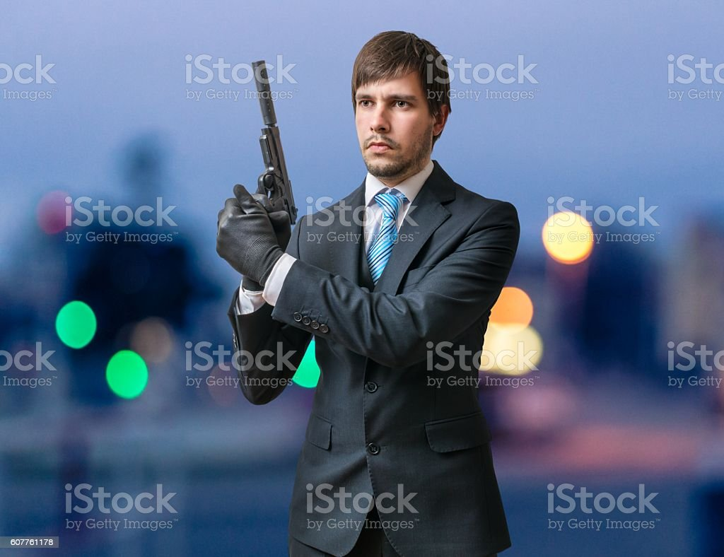 Agent with gun or pistol in hands at dusk. stock photo